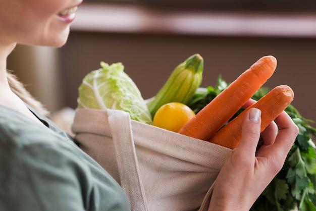 Mulher de close-up, segurando o saco reutilizável com legumes orgânicos