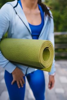 Mulher de close-up segurando roll fitness ou tapete de ioga depois de malhar no parque.