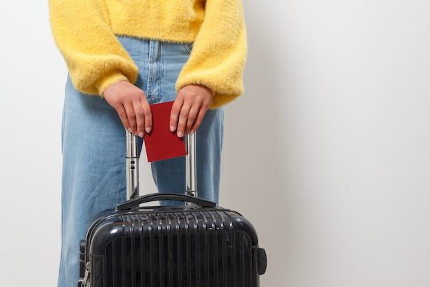 Mulher de close-up segurando um passaporte e uma mala de viagem nas mãos. viagem, imigração, conceito de emigração