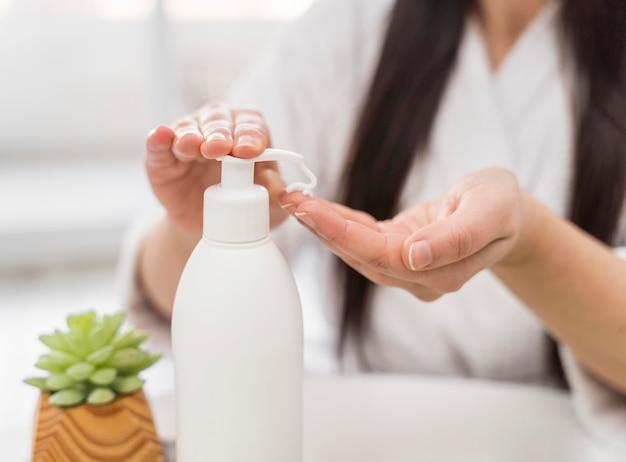 Mulher de close-up servindo creme para as mãos