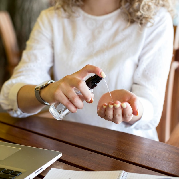 Mulher de close-up usando desinfetante para as mãos
