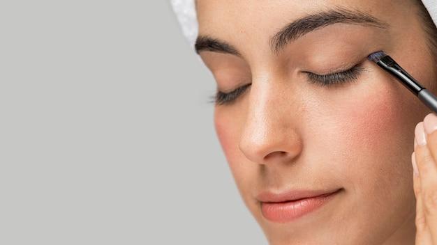 Mulher de close-up usando maquiagem