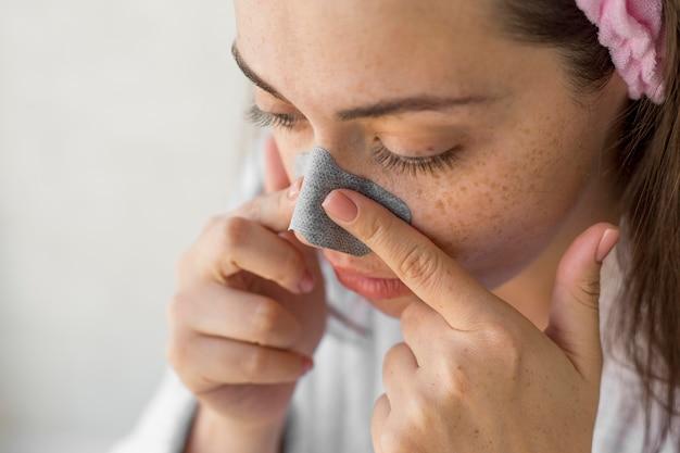 Mulher de close-up usando tapa-nariz