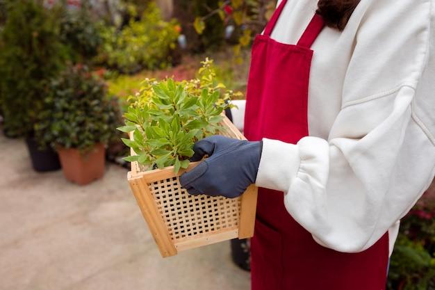 Mulher de close-up, vestindo roupas de jardinagem e segurando cesta em estufa