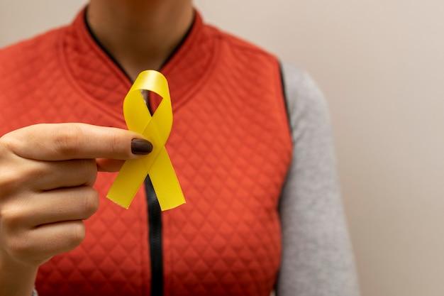 Mulher de colete segurando a fita amarela da campanha de segurança no trânsito. foco seletivo.