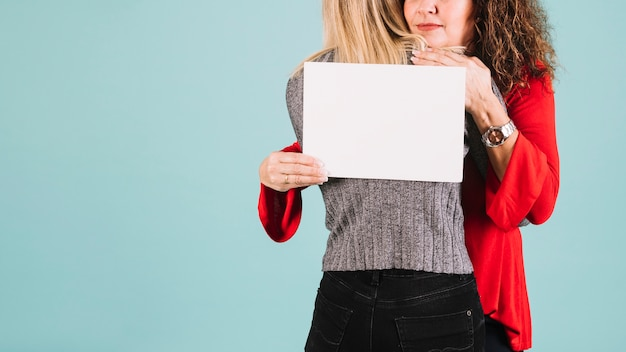 Mulher de colheita abraçar a filha e segurando a folha de papel
