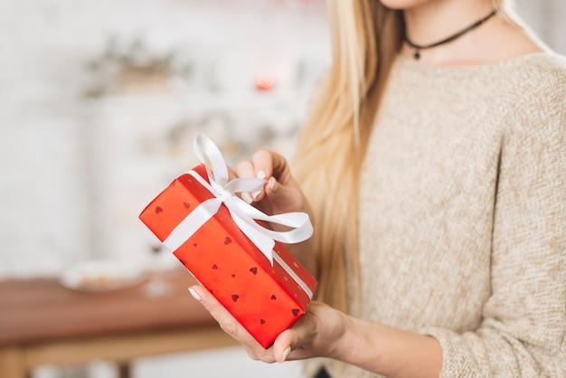 Mulher de colheita abrindo a caixa de presente vermelha