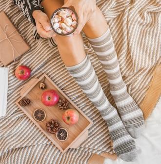 Mulher de colheita beber chocolate quente na cama