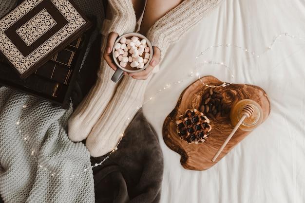 Mulher de colheita com chocolate quente perto de lanches