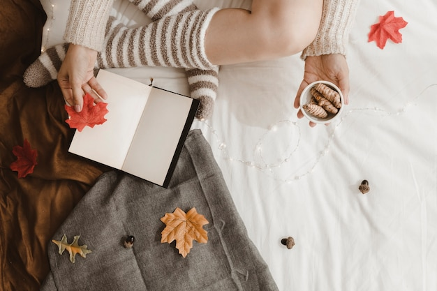 Mulher de colheita com folhas e gengibre perto de livro