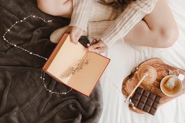 Mulher de colheita com livro perto de chá e doces