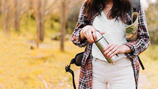 Mulher de colheita com mapa fechando a garrafa térmica