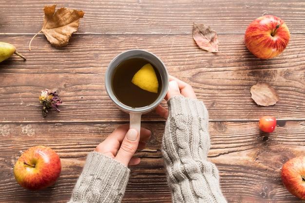 Mulher de colheita com xícara de chá de limão