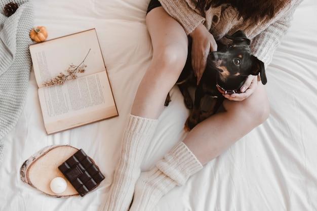 Mulher de colheita e cachorro perto de chocolate e livro