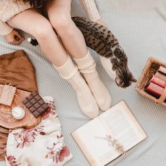 Mulher de colheita e gato no cobertor perto de livros e lanches
