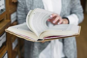 Mulher de colheita lançando páginas do livro