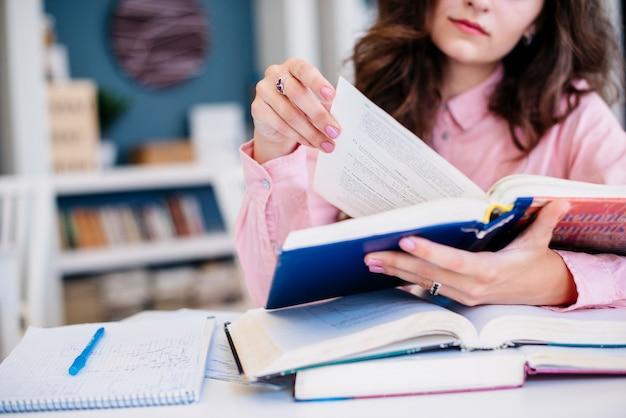Mulher de colheita lendo livros didáticos na biblioteca