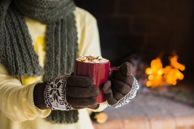 Mulher de colheita mostrando caneca de chocolate quente