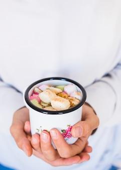 Mulher de colheita segurando a caneca com bebida e marshmallows
