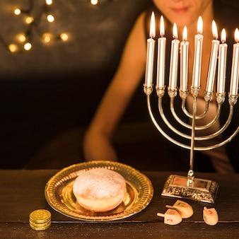 Mulher de colheita sentado perto de símbolos de hanukkah