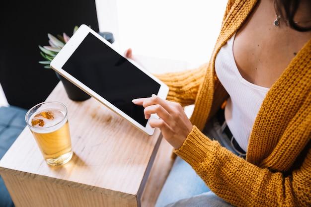 Mulher de colheita tocando na tela do tablet