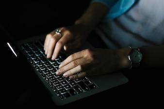 Mulher de colheita usando laptop no quarto escuro