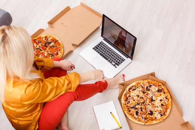 Mulher de comércio eletrônico. jovem mulher usando o computador para fazer compras online, sentada no chão e comendo pizza.
