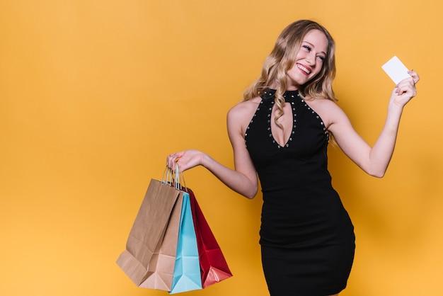 Mulher de compras brilhante com cartão de crédito