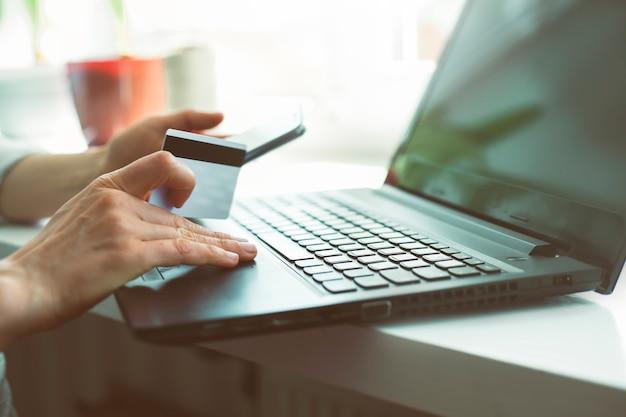 Mulher de compras on-line com um smartphone. as mãos da fêmea compram em linha guardarando um cartão de crédito com um portátil na tabela que senta-se em um café.