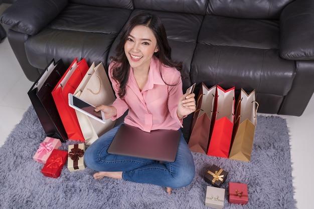Mulher de compras on-line para presente com o laptop na sala de estar