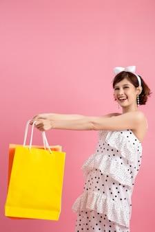 Mulher de compras segurando sacolas de compras em rosa