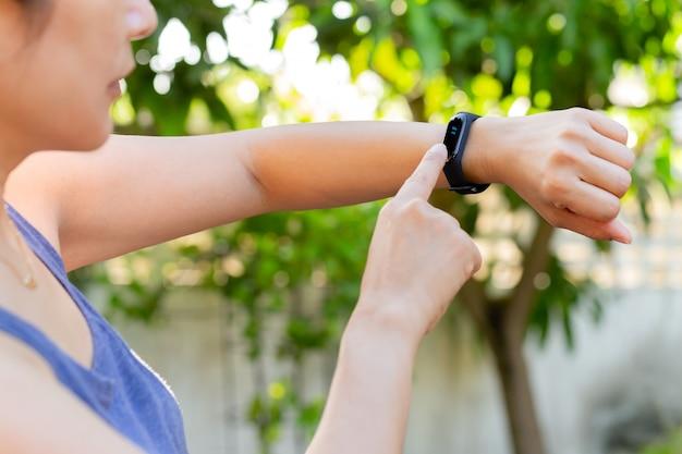 Mulher de conceito de cuidados de saúde, verificando o monitor de pulseira de aptidão no relógio inteligente