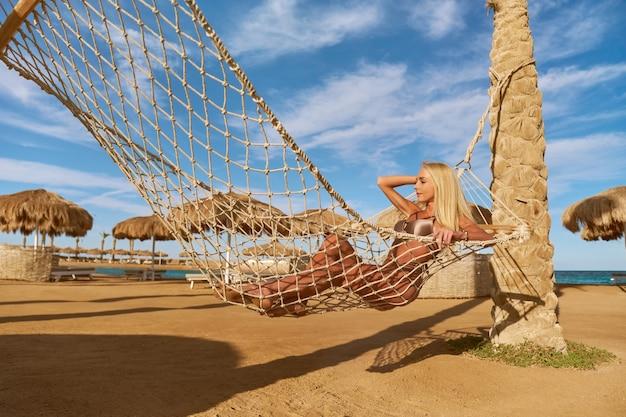 Mulher de conceito de viagens e férias relaxando em uma rede na praia
