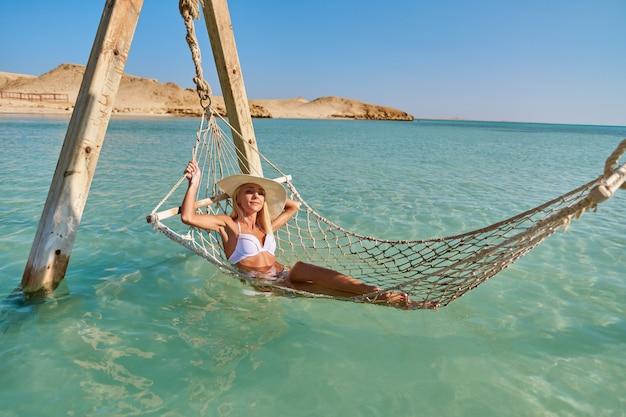 Mulher de conceito de viagens e férias relaxando em uma rede no mar