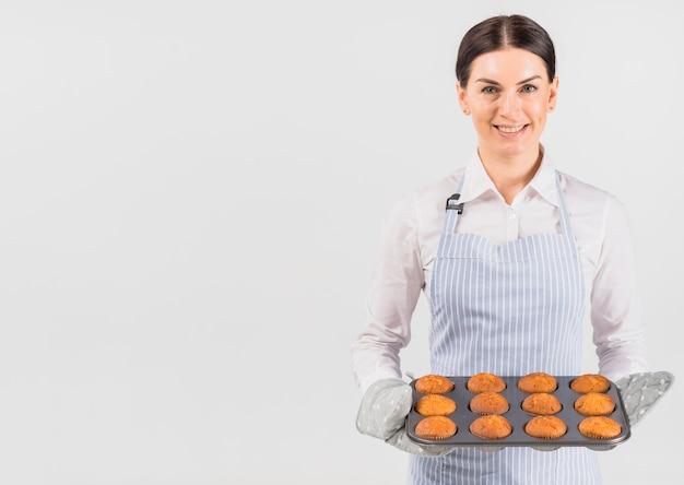 Mulher de confeiteiro sorrindo e segurando a lata de muffin