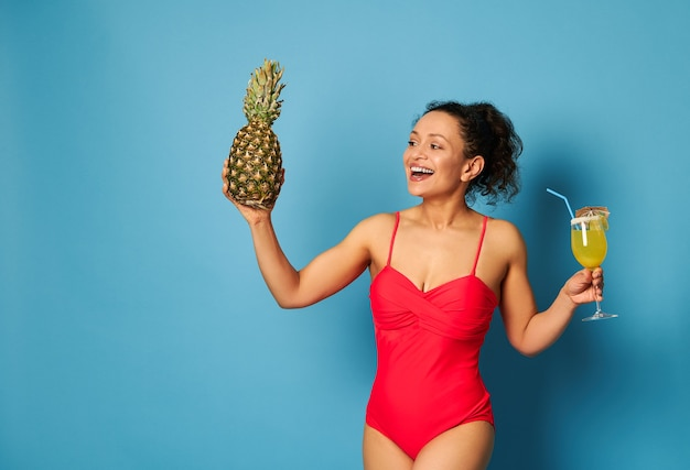 Mulher de construção muscular em um maiô vermelho com um abacaxi e um coquetel nas mãos posando