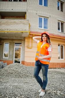 Mulher de construtor de engenheiro no colete uniforme e capacete protetor laranja contra novo edifício