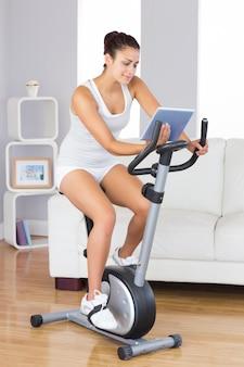 Mulher de conteúdo slim usando seu tablet enquanto treinava em uma bicicleta ergométrica