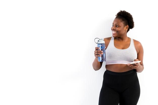 Mulher de cópia-espaço hidratante após o treino