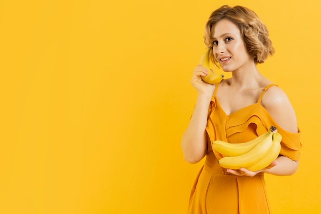 Mulher de cópia-espaço usando banana como móvel