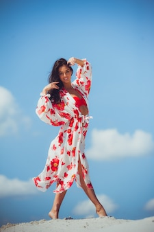 Mulher de corpo de biquíni sexy se sentindo livre com estômago magro e coxas lisas vestindo moda colorida cachecol saia moda praia swimwear mostrando a perda de peso. conceito de bem-estar do spa de beleza a laser.