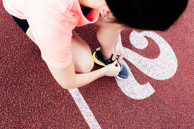 Mulher de corredor amarrar cadarços de tênis se preparando para a corrida