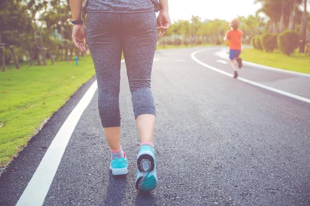 Mulher de corredor correndo de manhã no parque público.