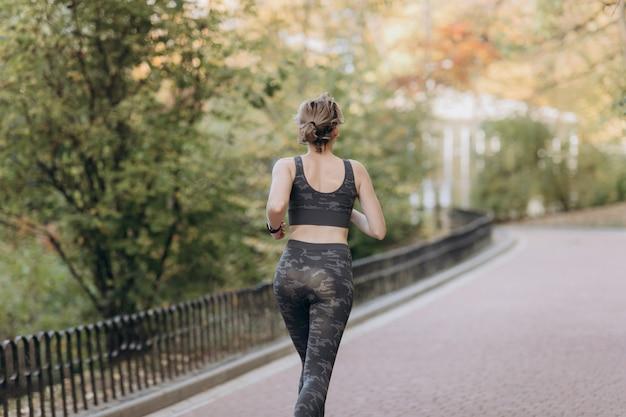 Mulher de corredor correndo no parque exercitar rastreador de fitness ao ar livre