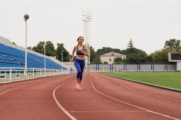 Mulher de corredor treinando no estádio
