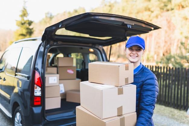 Mulher de correio de conteúdo com pilha de caixas