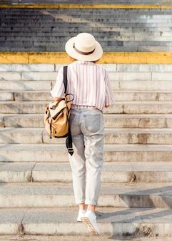 Mulher de costas caminhando pelas escadas do lado de fora