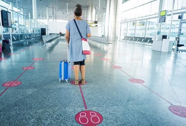 Mulher de costas com mala esperando no aeroporto mantendo distanciamento social distância social para evitar covid