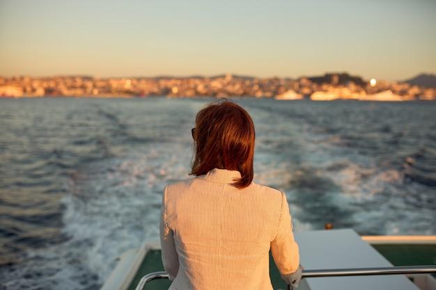 Mulher de costas na garupa de um barco, observando enquanto ele se afasta do porto da cidade.