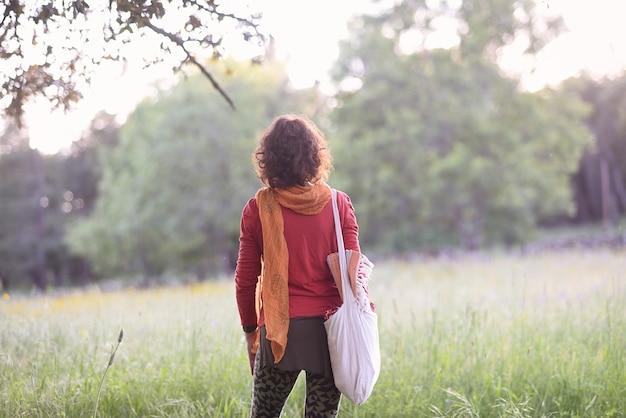 Mulher de costas para a natureza com suas ferramentas de ioga